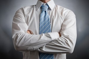 Image of a man wearing a shirt and tie with arms crossed